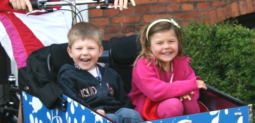 2 glade børn i en BellaBike ladcykel