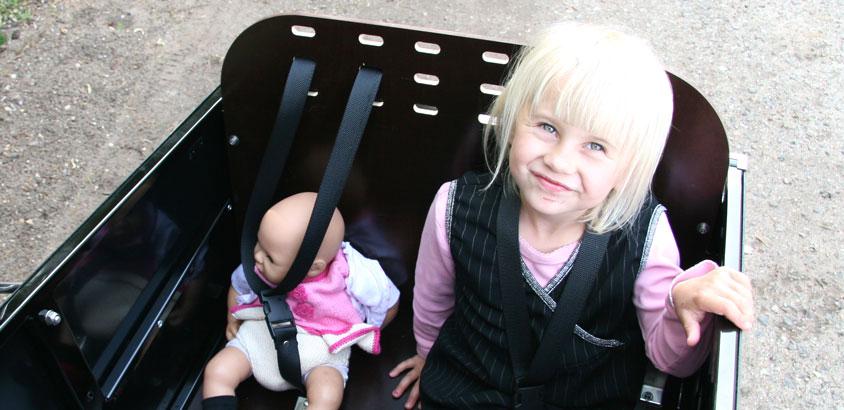 En pige med sin dukke i ladcyklen