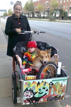 Et barn og en hund sidder begge i Louise Shonemanns ladcykel