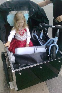 En lille pige sidder i en ladcykel med sin egen cykel med i kassen