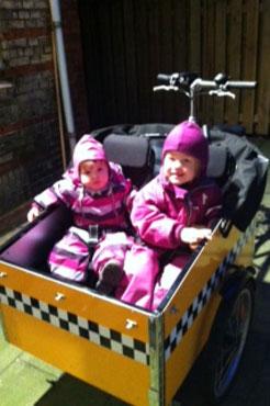 To piger nyder at sidde i en fantastisk, stribet ladcykel